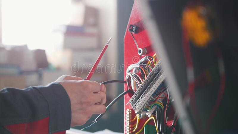 Electrician`s hands installing energy system on machinery industry. Close up royalty free stock images