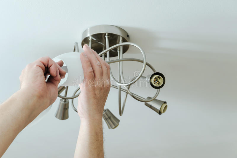 Electrician`s hands are installing a LED bulb. Electrician`s hands are installing a LED light bulb in a lamp stock images