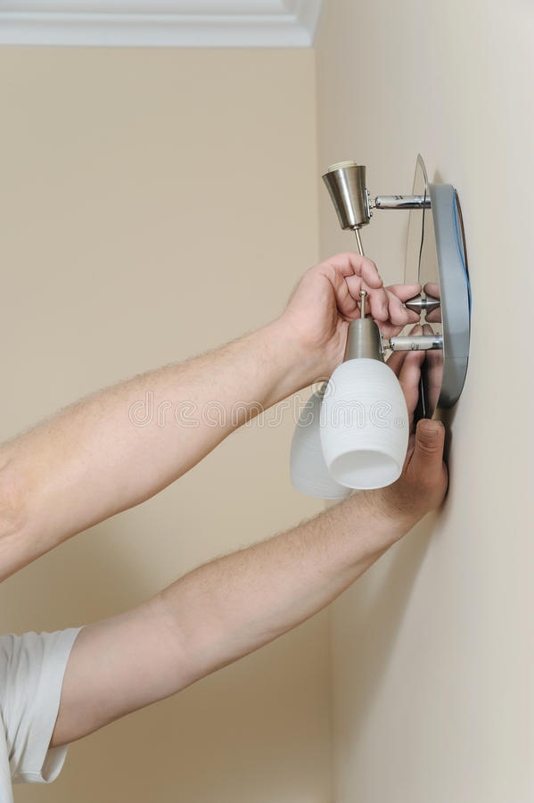 Electrician`s hands are instilling a wall lamp stock photo