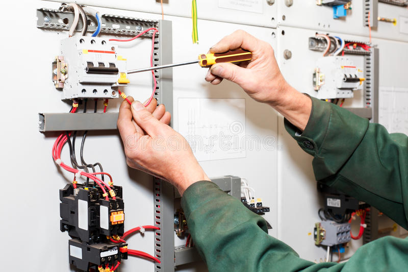 Electrician`s hands working stock photos