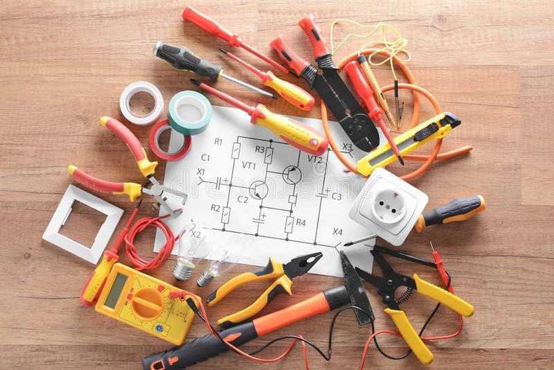 Electrician's supplies and circuit diagram on wooden background stock image