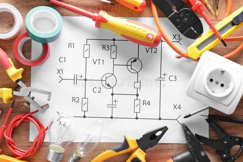 Electrician\'s supplies and circuit diagram on wooden background royalty free stock photos