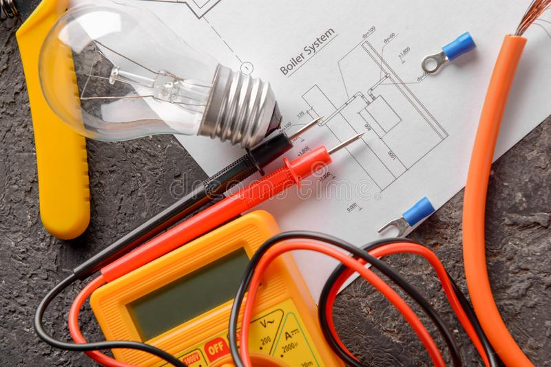 Electrician's supplies with house plan on grey background royalty free stock photos