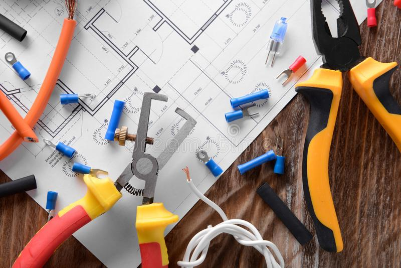 Electrician's supplies with house plan on table royalty free stock images