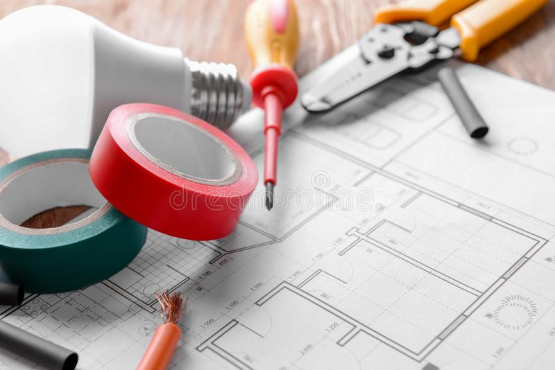 Electrician's supplies with house plan on table, closeup stock image