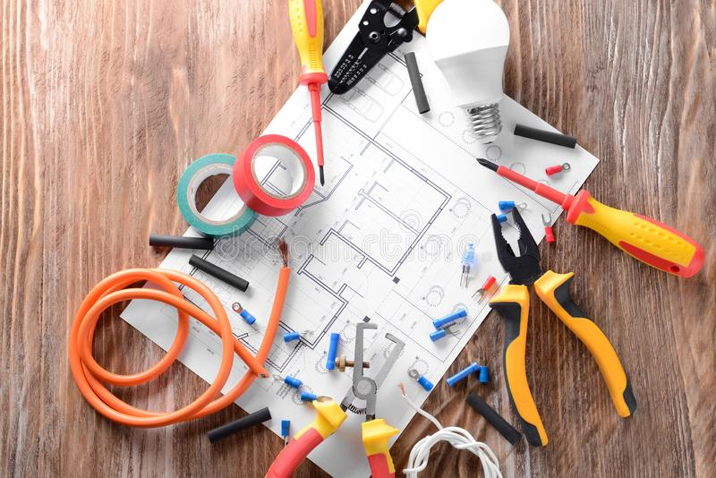 Electrician\'s supplies with house plan on wooden background stock images