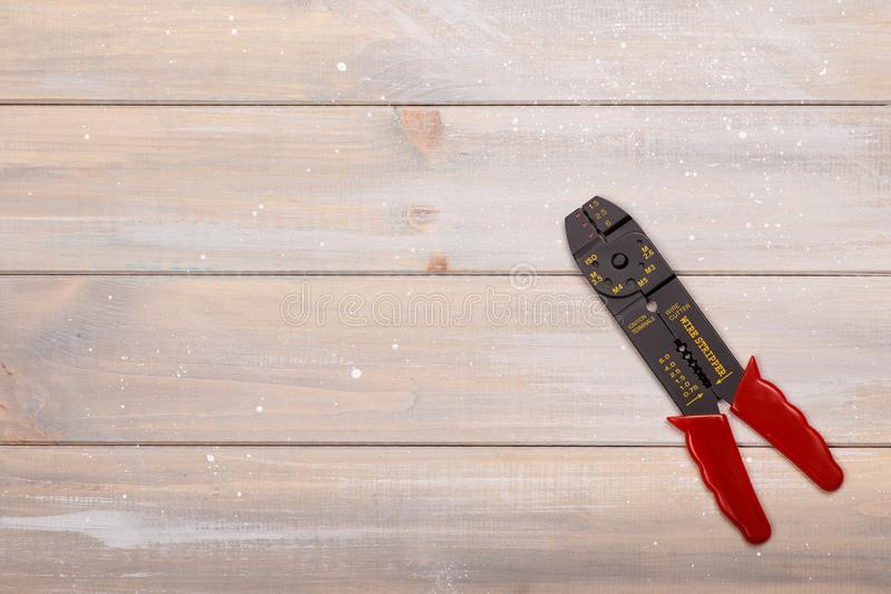Electrician`s tool lies on the wooden table stock image