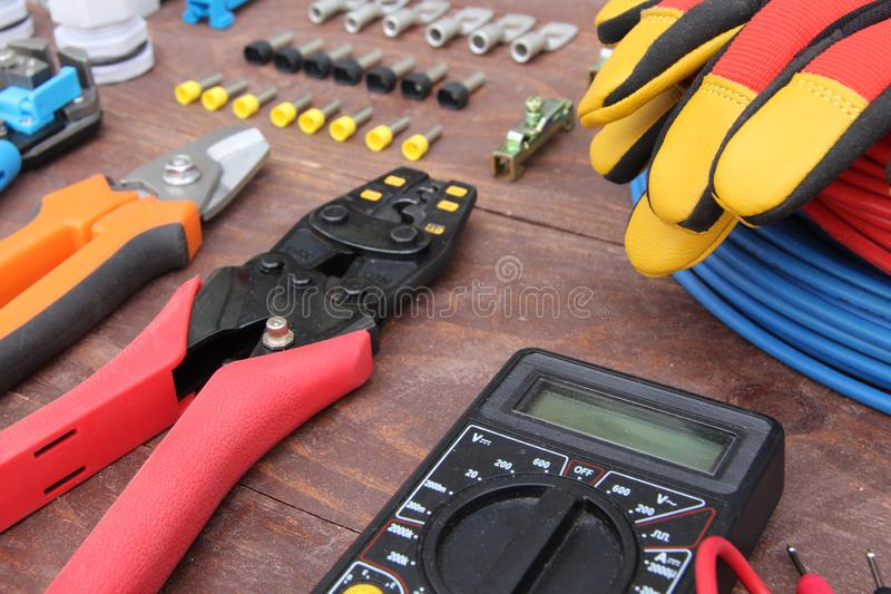 Electrician tools with red and blue wire laid out on a wooden surface of dark color stock images