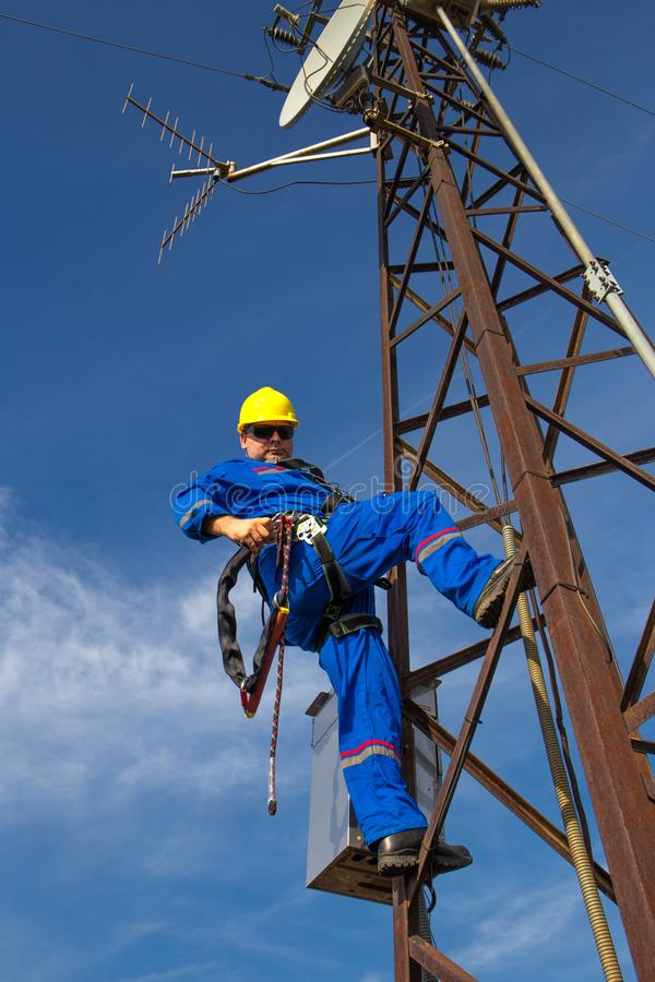 Electrician with safety belt climb on electric power pole stock photos
