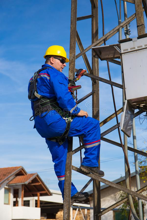 Electrician with safety belt working on electric power pole stock image