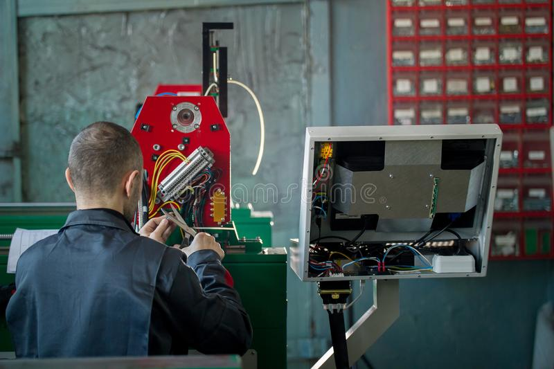 Electrician with scissor is installing energy system on machinery industry. Close up stock photo
