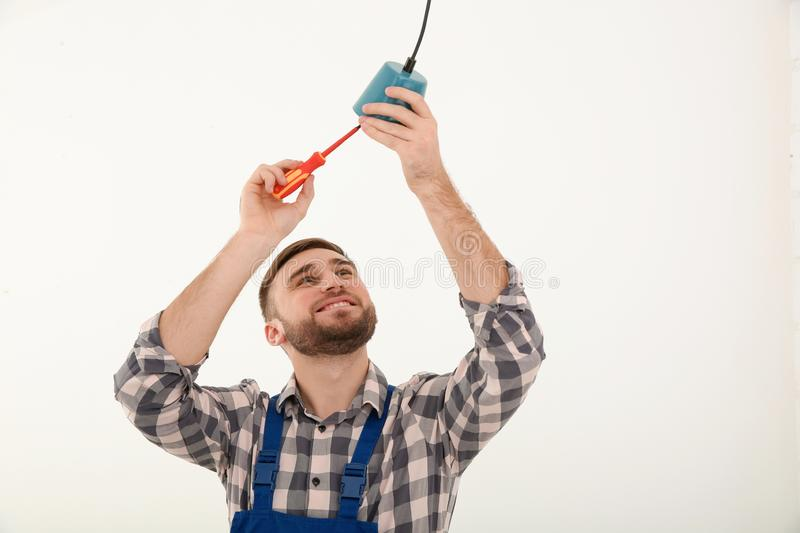 Electrician with screwdriver repairing ceiling lamp. Against white background royalty free stock photography