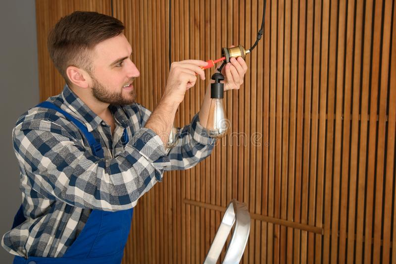 Electrician with screwdriver repairing ceiling lamp. Space for text stock images