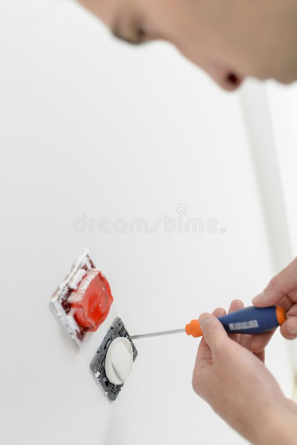 Electrician screwing socket to wall royalty free stock photos