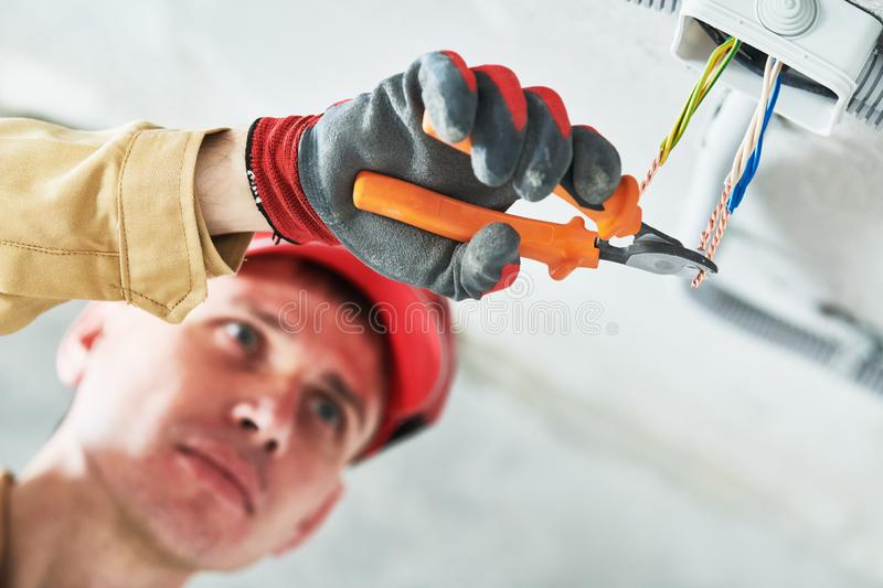 Electrician service. Installer works with cable in junction box stock photo