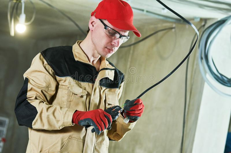 Electrician service. Installer works with cable stock image