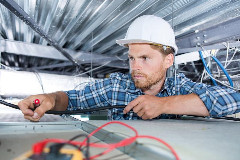 Electrician sets lamp on ceiling stock photos