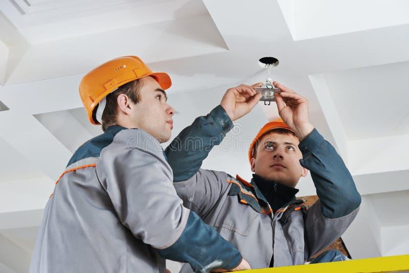 Electrician at spot light installation royalty free stock photos