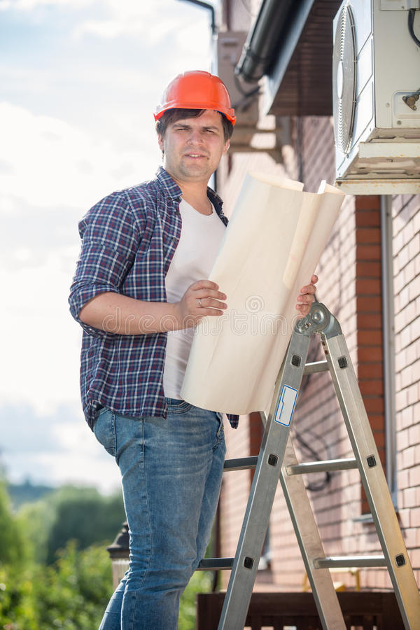 Electrician standing on high stepladder and holding plan of house stock photo