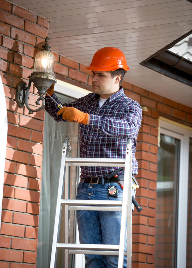 Electrician standing on ladder and changing outdoor lamp royalty free stock images