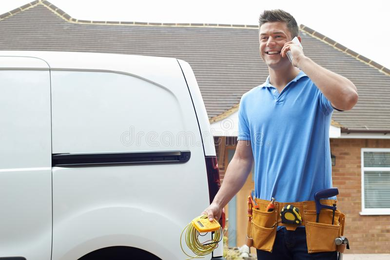 Electrician Standing Next To Van Talking On Mobile Phone. Electrician Stands Next To Van Talking On Mobile Phone royalty free stock images