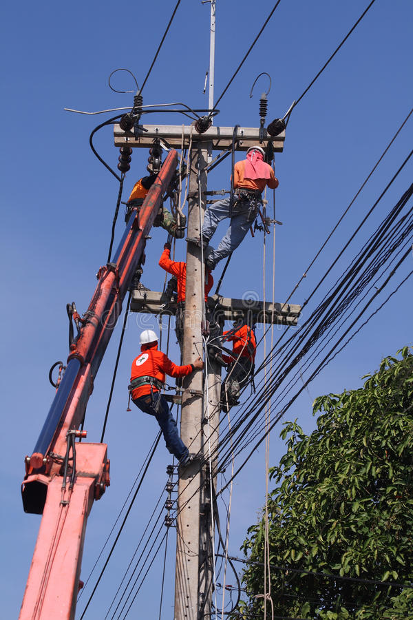 Electrician stays. On the tower pole and repairs a wire of the power line stock image