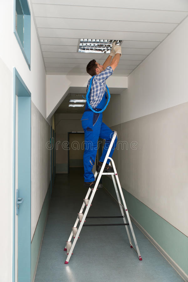 Electrician on stepladder installs lighting to the ceiling royalty free stock photography