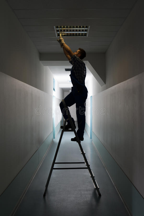 Electrician on stepladder installs lighting to the ceiling. Full length side view of electrician on stepladder installs lighting to the ceiling in office royalty free stock image