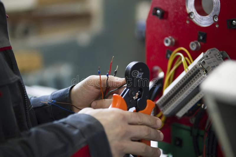Electrician with stripper installing energy system on machinery industry. Close up stock photos
