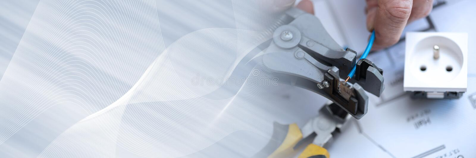 Electrician stripping a wire; panoramic banner stock photography