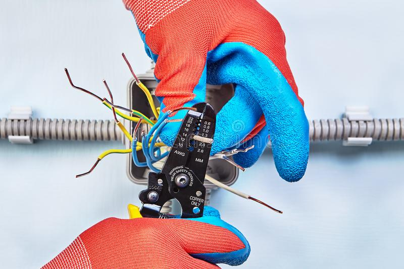 Electrician is stripps wires with stripper tool royalty free stock photos
