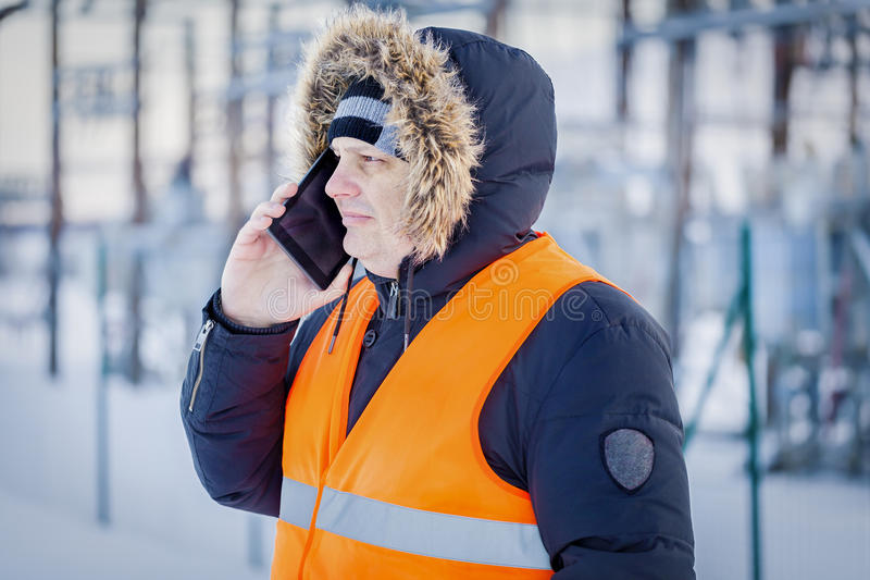 Electrician talking on smart phone at power plant in winter stock image