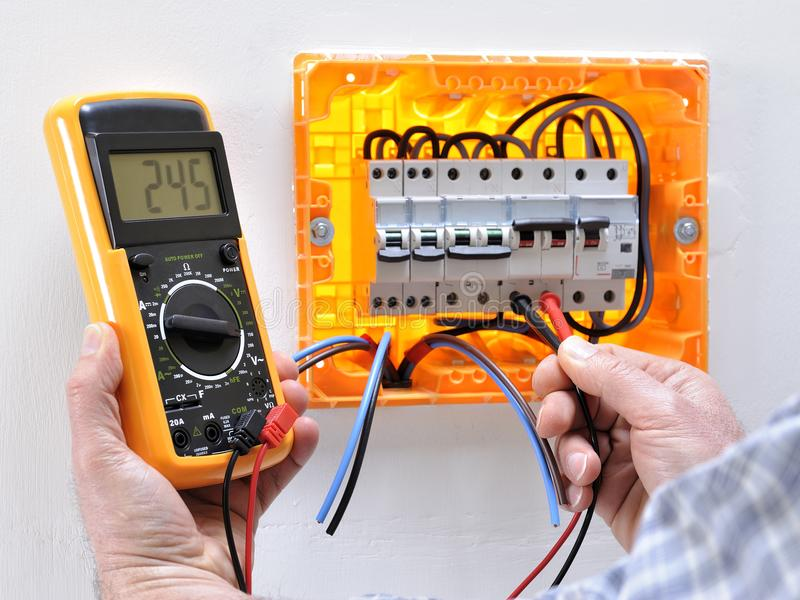 Electrician technician at work on a residential electric panel royalty free stock photo