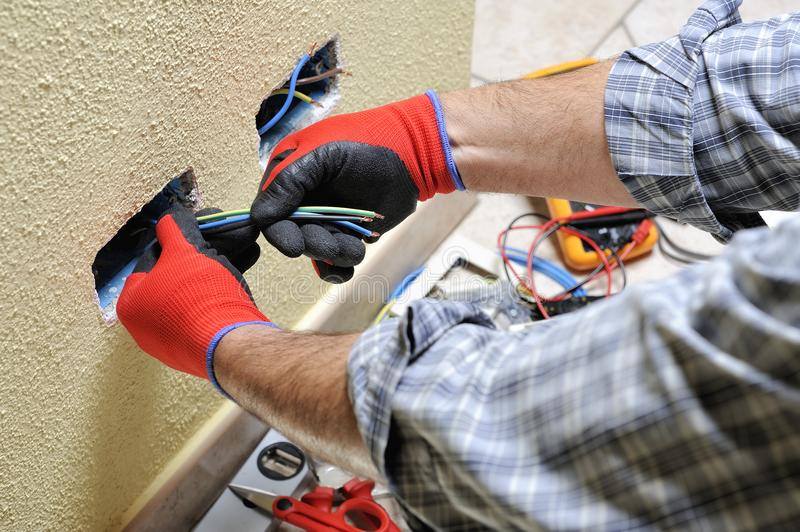Electrician technician at work with safety equipment on a residential electrical system stock image