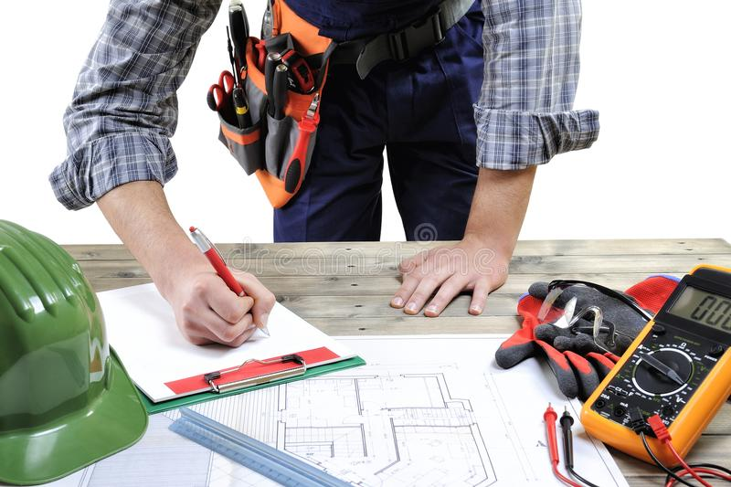 Young electrician technician analyzes the project of a residential building royalty free stock photo