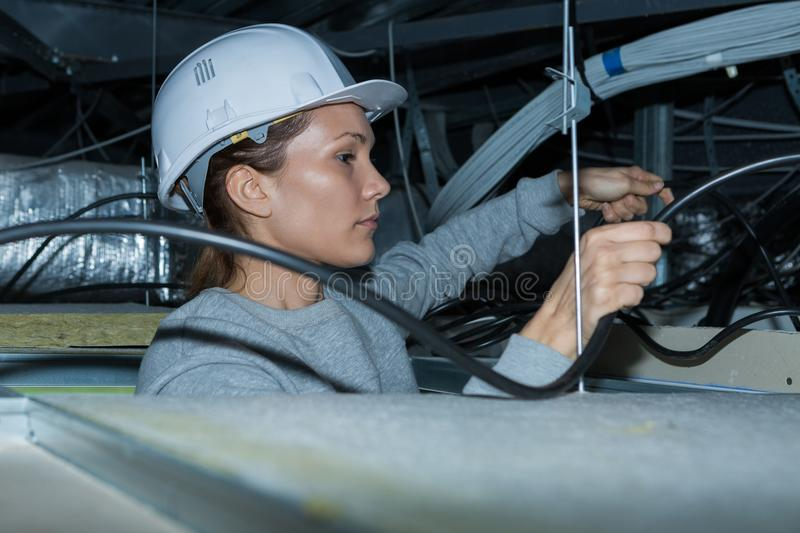 Electrician tending to wiring in roof space. Electrician royalty free stock image