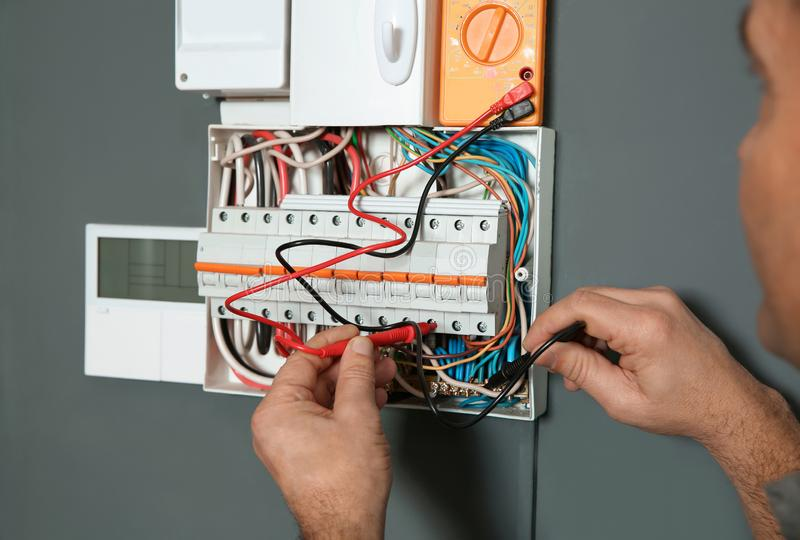Electrician with tester checking voltage indoors royalty free stock image
