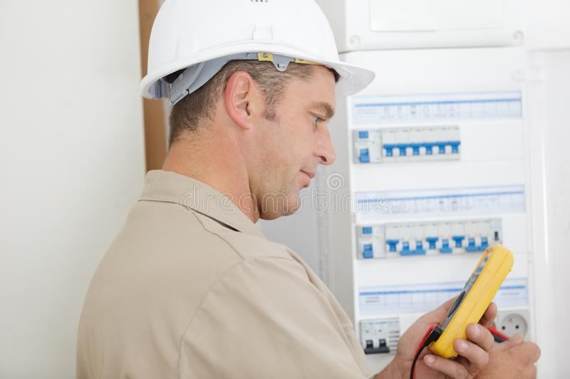 Electrician testing circuit breaker cabinet with multimeter royalty free stock photos