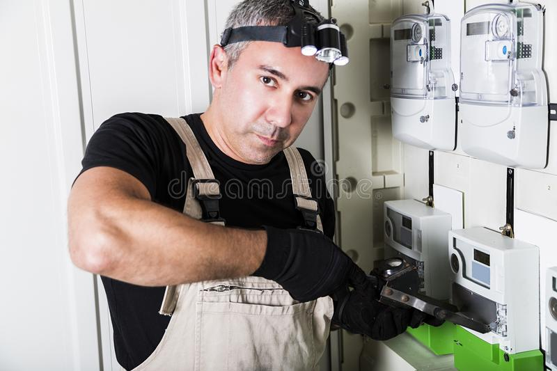 Electrician testing fuse box or switch box with flashlight on head close-up royalty free stock photography