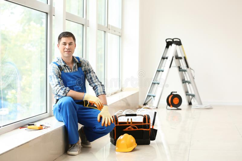 Electrician with toolbox sitting on windowsill in new empty apartment royalty free stock photography