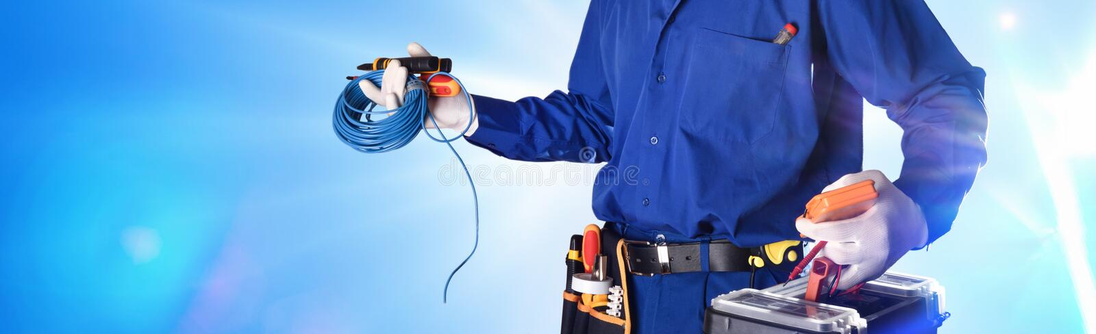 Electrician with tools and electrical equipment isolated with lights. Background with uniformed electrician with tools and electrical equipment and blue stock photo