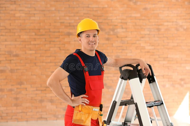 Electrician with tools and ladder in new empty apartment royalty free stock photography