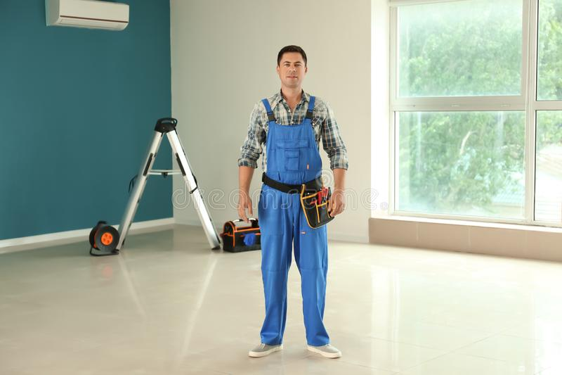 Electrician with tools in new empty apartment stock image
