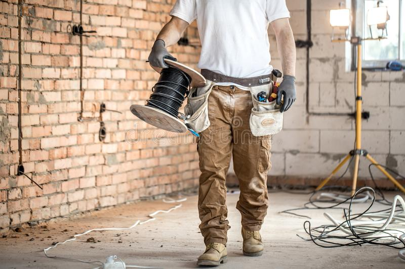 Electrician with tools, working on a construction site. Repair and handyman concept. House and house reconstruction stock images