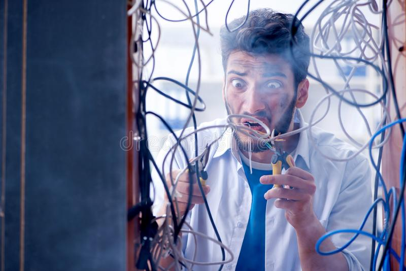 The electrician trying to untangle wires in repair concept stock image