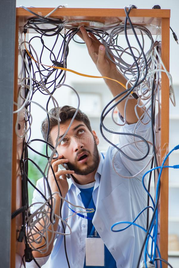 The electrician trying to untangle wires in repair concept royalty free stock image