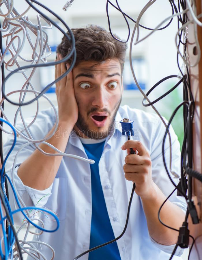 Electrician trying to untangle wires in repair concept. The electrician trying to untangle wires in repair concept royalty free stock images