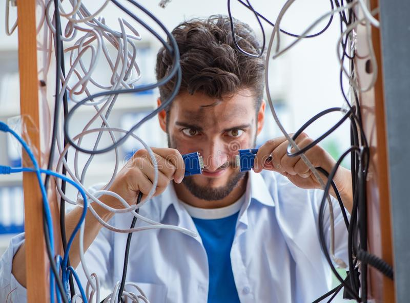 Electrician trying to untangle wires in repair concept. The electrician trying to untangle wires in repair concept stock photography