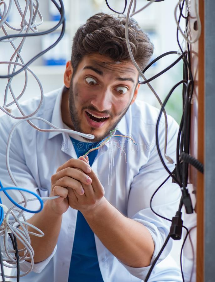 Electrician trying to untangle wires in repair concept stock photography