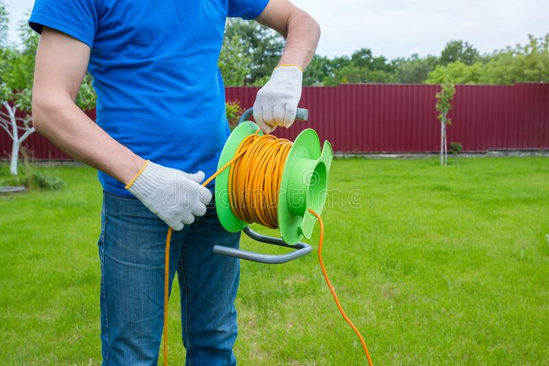 An electrician is unrolling an extension cord on the coil in the house backyard. Cleaning of the territory stock photos